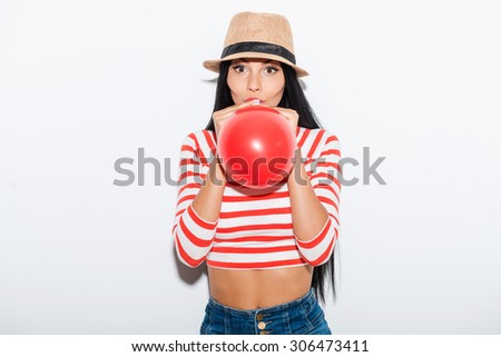 Baloon fun. Playful young woman blowing red balloon while standing against white background - stock photo
