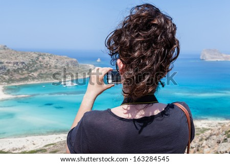Balos beach, Crete, Greece, Tourist taking a picture with your mobile phone - stock photo