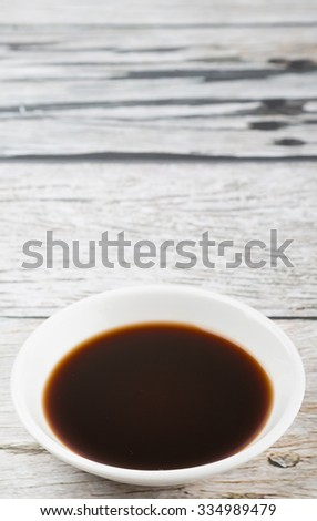 Balsamic vinegar in a white bowl over wooden background - stock photo