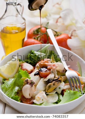 balsamic vinegar over mixed seafood salad with mozzarella and avocado - stock photo