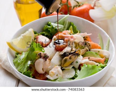 balsamic vinegar over mixed seafood salad with mozzarella and avocado - stock photo
