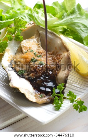 balsamic vinegar over oyster au gratin - stock photo