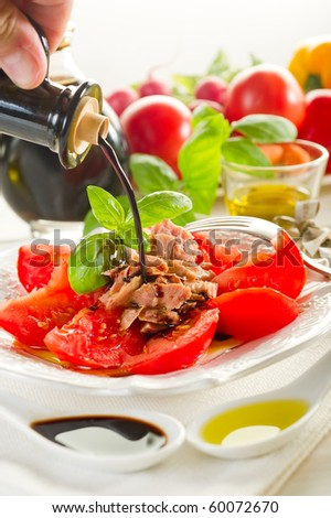 balsamic vinegar over salad with tuna and tomatoes - stock photo