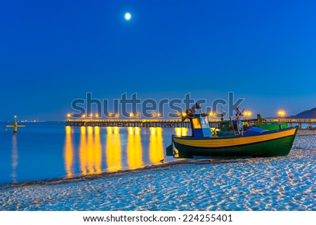 Baltic beach with fishing boat at night, Poland - stock photo
