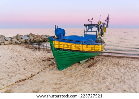Baltic beach with fishing boat at sunset, Poland