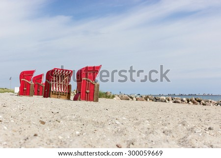 Baltic Sea beach with red beach chairs and blue sky / beach chairs by the sea / Baltic Sea - stock photo