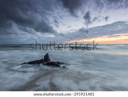 Baltic sea coast at sunset, with trunks and roots of the forest drowned by the advancing sea in Rowy, near Ustka, Poland - stock photo