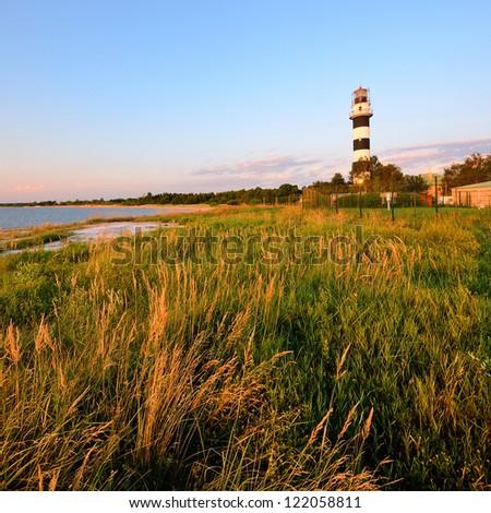 Baltic sea shore with lighthouse at the sunset. Riga, Latvia - stock photo