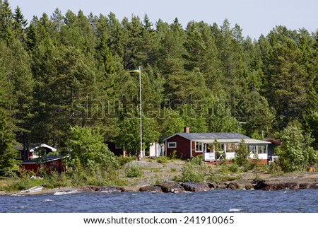 BALTIC SEA, SWEDEN ON JUNE 29. The Swedish archipelago along the shore on June 29, 2011 in The Baltic Sea, Sweden. Red lodges, cabins by the sea. Forest and rocks.