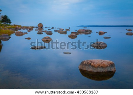 Baltic seaside after sunset with stones in water, long exposure - stock photo