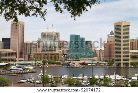 Baltimore city inner harbor showing the city skyline, ship, and pleasure craft docks and boardwalk. - stock photo