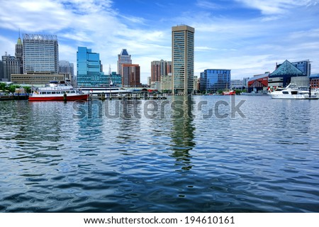 Baltimore Inner Harbor water view with shopping centers and cruise boats near National Aquarium and downtown business district buildings and shops in a cityscape skyline of the scenic Maryland city