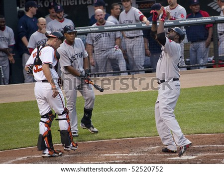 BALTIMORE - MAY 1: David Ortiz of the Boston Red Sox celebrates at home plate after hitting one of two home runes during a game at Camden Yards on May 1, 2010 in Baltimore, Maryland - stock photo