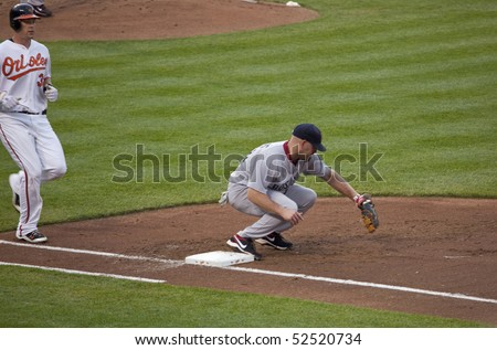BALTIMORE - MAY 1: Kevin Youkilis of the Boston Red Sox picks a ball at first base during a game at Camden Yards on May 1, 2010 in Baltimore, Maryland - stock photo