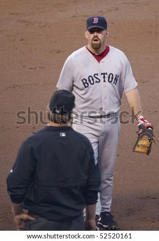 BALTIMORE - MAY 1: Kevin Youkilis of the Boston Red Sox stands at first base talking to an umpire during a game at Camden Yards on May 1, 2010 in Baltimore, Maryland - stock photo