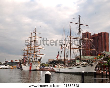 BALTIMORE, MD -  SEPTEMBER 11, 2014: Tall ship Gazela, and US Coast Guard ship Eagle are moored at the Inner Harbor in downtown Baltimore for the Star Spangled Spectacular event. - stock photo