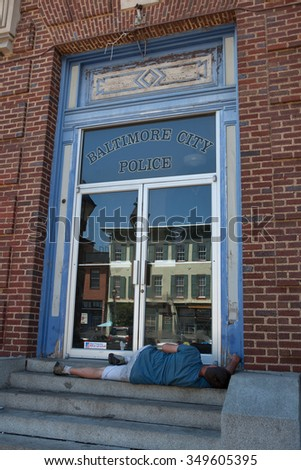 Baltimore, MD, USA - July 26, 2011: A street person sleeps on the steps of the building had been featured as police headquarters for NBC'??s  Homicide: Life on the Street. - stock photo