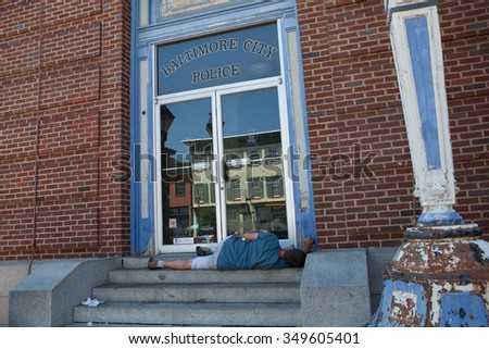 Baltimore, MD, USA - July 26, 2011: A street person sleeps on the steps of the building that had been featured as police headquarters for Homicide: Life on the Street. - stock photo