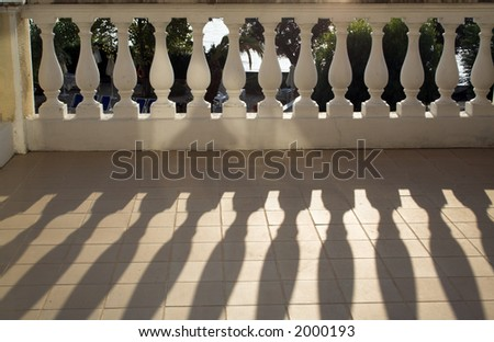 Balustrade casting shadows in sunshine on the balcony floor - stock photo