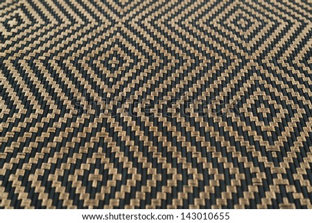 Bamboo black straw mat with a golden ornament as a background composition with a shallow depth of field