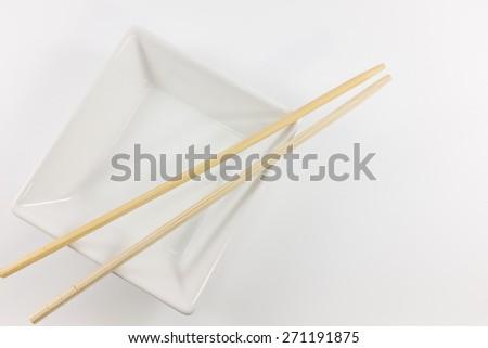 Bamboo chopsticks and ceramic on white background. - stock photo