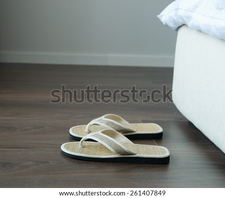 Bamboo flip flops on the ground near bed. - stock photo