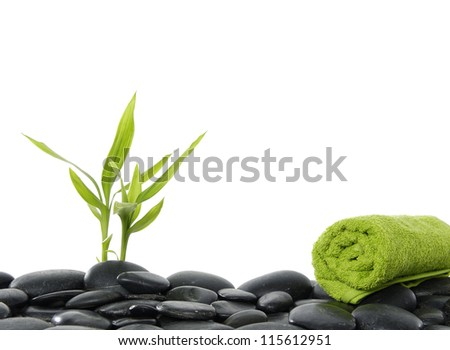 Bamboo leaf and basalt stones with green towel - stock photo