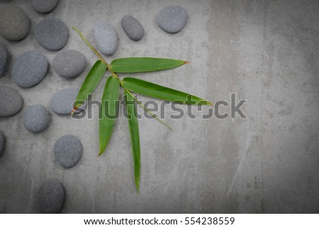 bamboo leaves on pile of gray stones with candle -gray background