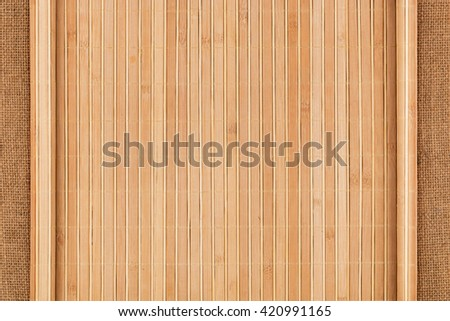 Bamboo mat twisted in the form of a manuscript on sackcloth, with space for your text - stock photo