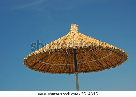 bamboo parasol against the blue sky - stock photo