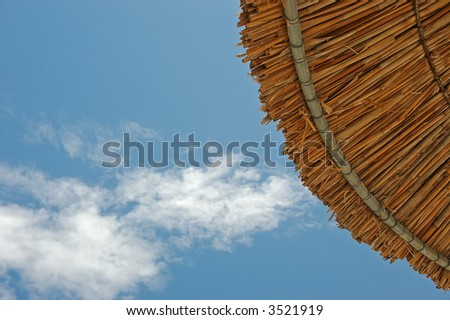 Bamboo parasol against the cloudy blue sky - stock photo