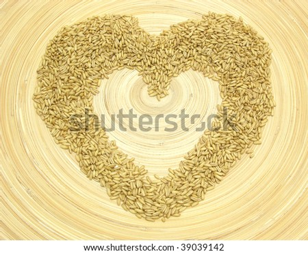 Bamboo plate with heart out of grain - stock photo