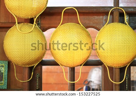 Bamboo sieves with handle hanging on window wall, hand made sieves - stock photo