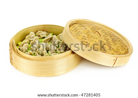 Bamboo steamer with cooked dumplings isolated on white - stock photo