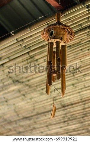 Bamboo windchime. Wind bell on the ceiling on bamboo wall background.