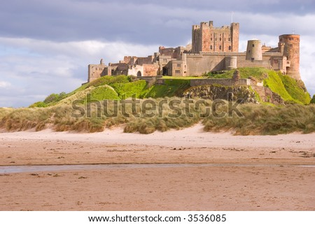 Bamburgh Castle overlooking the beach - stock photo