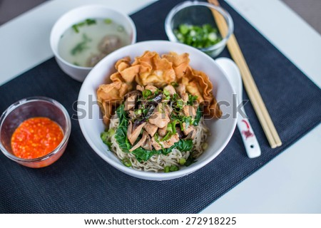 Bami Ayam, a traditional Indonesian chicken noodle dish, complete with fried wonton, vegetables, meat ball soup and chili sauce. - stock photo