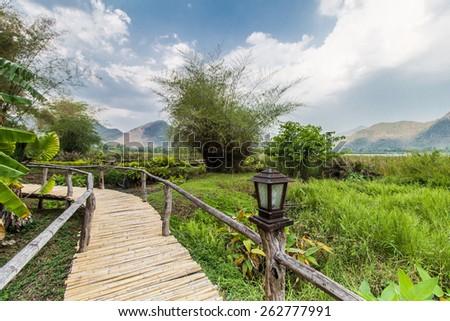 Bammboo bridge near reservoir with mountain and sky view in Karnchanaburi,Thailand - stock photo