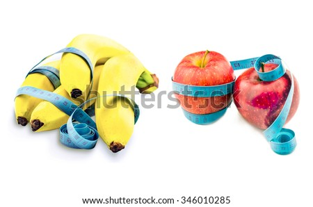Banana and apple wrapped in measuring tape on a white background