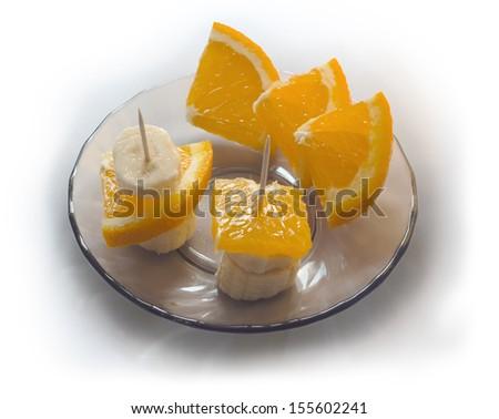 Banana and orange on a saucer - stock photo