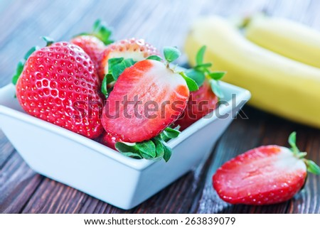 banana and strawberry on the wooden table - stock photo