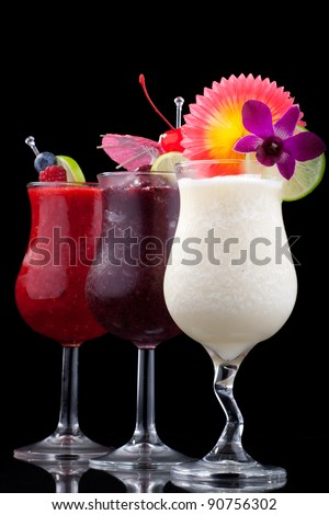 Banana, Blueberry and Raspberry Daiquiri cocktails. Rum, banana, blueberries, raspberry, liqueur, lime juice garnished with lime and fresh raspberries over black background. - stock photo