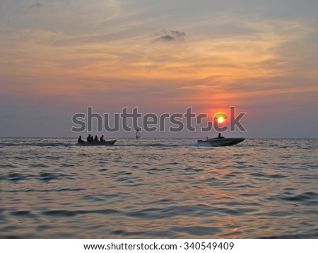 banana boat into the sea with sunset