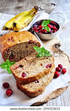Banana bread loaf with ripe bananas and frozen cranberries for breakfast on rustic background, selective focus - stock photo