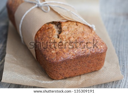 Banana bread with nuts in the baking paper on the wooden table, selective focus - stock photo