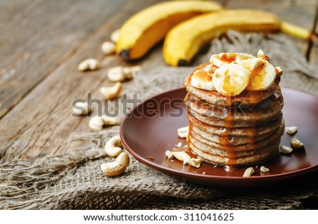 banana cashew pancakes with bananas and salted caramel sauce. the toning. selective focus - stock photo