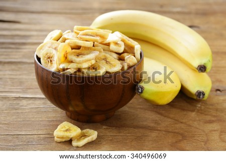 banana chips, dried fruit on a wooden table - stock photo
