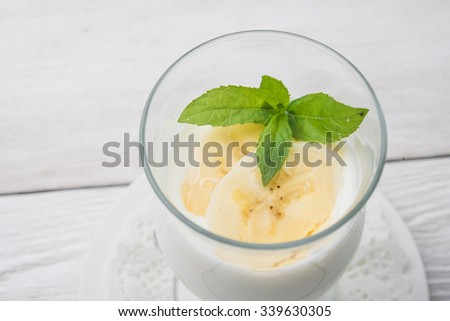 banana cocktail with green mint on white wooden table