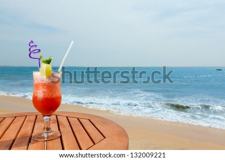banana daiquiri cocktail with ice on the table against the background of sea and sky - stock photo