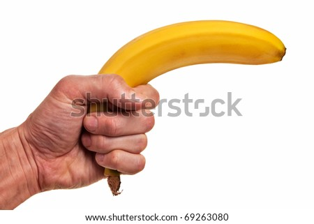 Banana fruit gun hold in caucasian white male hand over white background. - stock photo